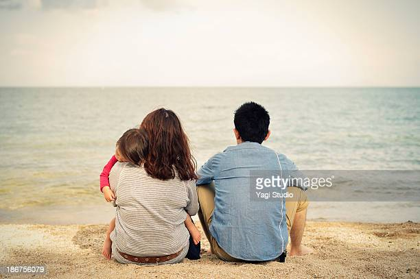 Family sit on the beach