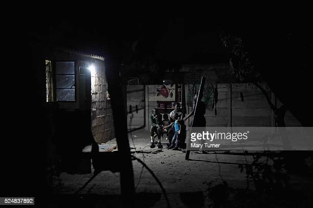 A family sit outside and share food by torchlight after darkness falls in the Harare suburb of Chitungwiza where electricity is only provided for a...