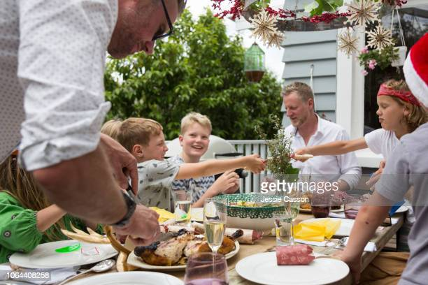 a family sit outside eating christmas lunch and pulling christmas crackers - lunch stock pictures, royalty-free photos & images