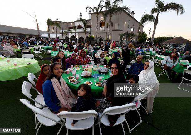 A family sit together as they break their Ramadan fast after sunset by eating halal Mexican tacos from a food truck during a campaign called 'Taco...