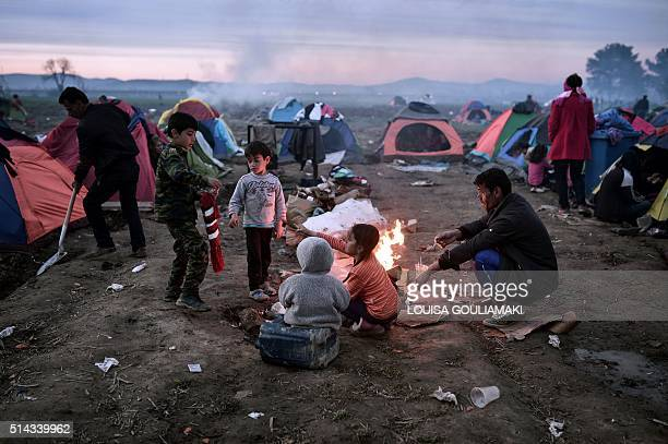 A family sits around a bonfire at the makeshift camp of the GreekMacedonian border near the village of Idomeni on March 8 where thousands of refugees...