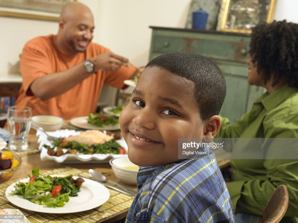 Family Sits at a Table With Food, Boy Looking at Camera : Stock Photo