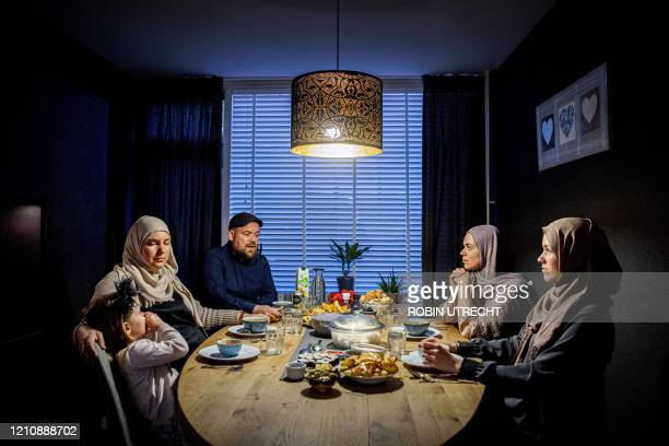A family sits at the table during the iftar the meal after sunset during the Islamic fasting month of Ramadan in Rotterdam on April 24 2020 Muslims...