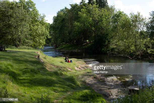 Family sits beside the River Teme on 23rd May 2020 near Martley, United Kingdom. Martley is a village and civil parish in the Malvern Hills district...