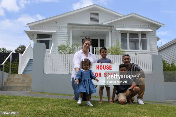 family sits in front of a home for sale - rafael ben ari stock-fotos und bilder