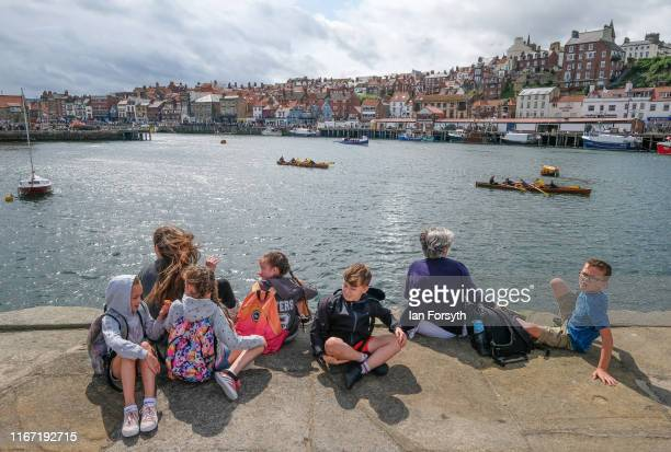 A family sits on the harbour wall watching events during the annual Whitby Regatta on August 10 2019 in Whitby England At over 170 years old the...