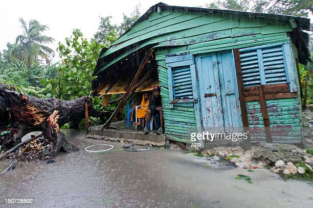 A family sits outside their house after the passage of Tropical Storm Isaac in Barahona southwestern Dominican Republic on August 25 2012 Tropical...
