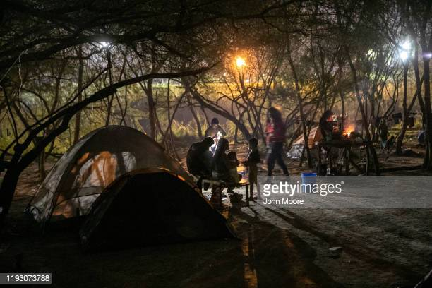A family sits outside their tent at a camp for asylum seekers on December 08 2019 in the border town of Matamoros Mexico More than 1000 Central...