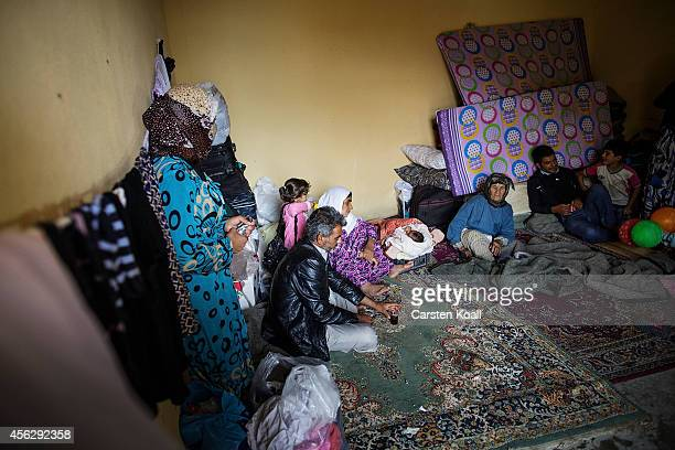 A family sits surounded by their belongings in a temporary room in a refugee camp after crossing from Syria into Turkey in Suruc September 28 2014...