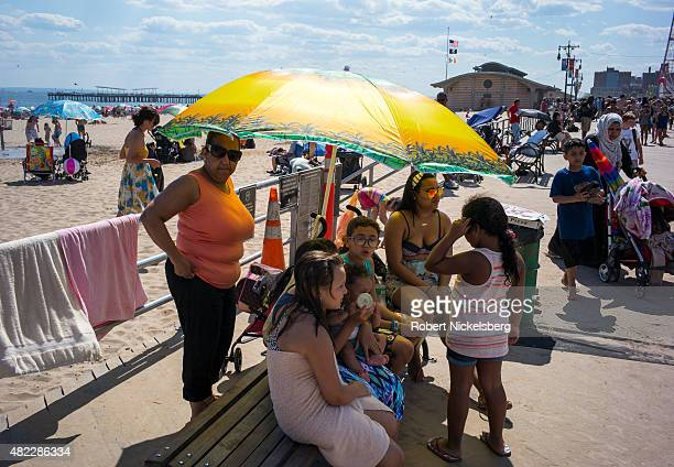 A family sits under an umbrella along the boardwalk July 24 2015 at Coney Island Beach in the Brooklyn borough of New York