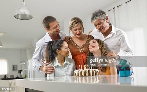 Family sitting around a birthday cake