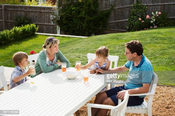 A family sitting around a garden table, parents and two children, a boy and a girl.