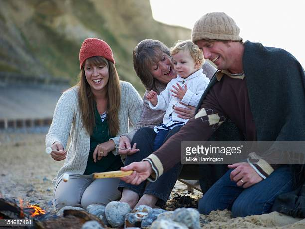 Family sitting around fire on beach
