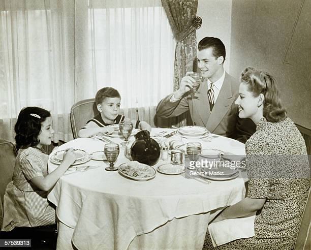 Family Sitting Around Table Having Meal Children 4 5 6