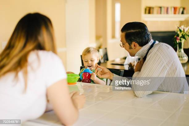 family sitting at kitchen table, young son holding sippy cup, father putting on neck tie - heshphoto fotografías e imágenes de stock