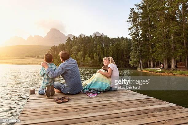 Family sitting at lake.