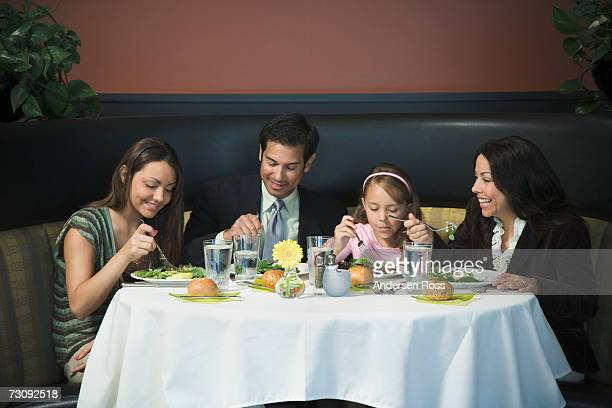 Family sitting at restaurant table, eating meal