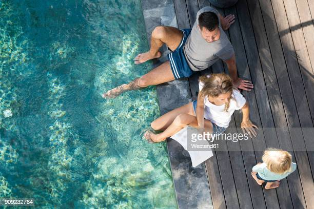 family sitting at the swimming pool, mother reading book for children - family vacation stock pictures, royalty-free photos & images