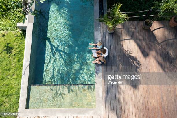 Family sitting at the swimming pool, mother reading book for children