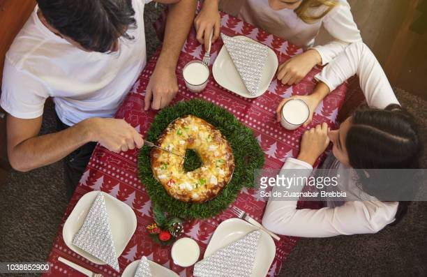 family sitting at the table about to cut a roscón de reyes (or rosca de pascua) - roscon de reyes stock pictures, royalty-free photos & images