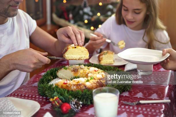 family sitting at the table, father serving slices of a roscón de reyes - roscon de reyes stock pictures, royalty-free photos & images