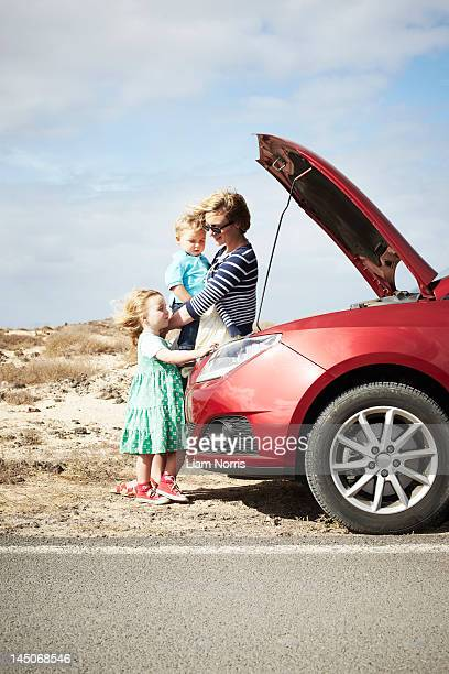 Family sitting by broken down car
