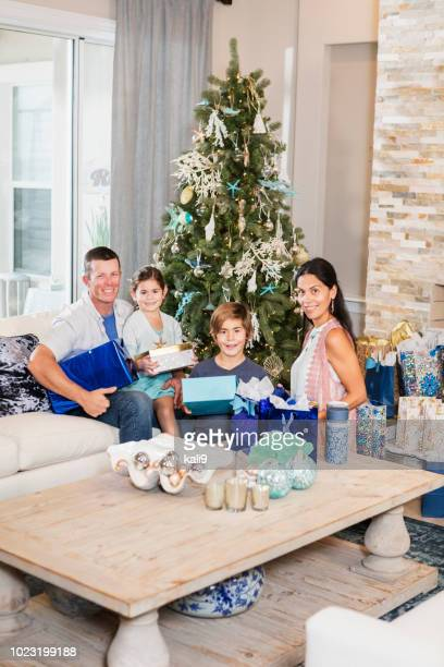 family sitting by christmas tree holding gifts - southern christmas stock pictures, royalty-free photos & images