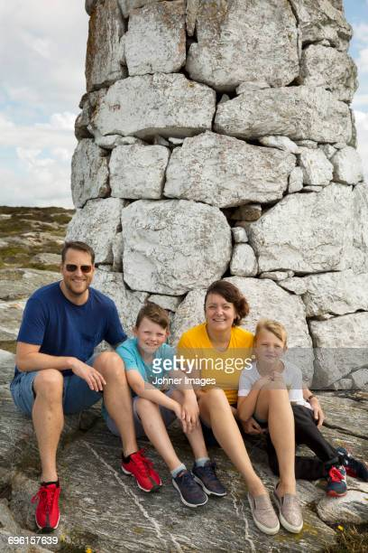 Family sitting by stone building