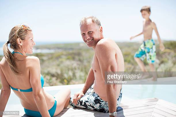 Family sitting by swimming pool