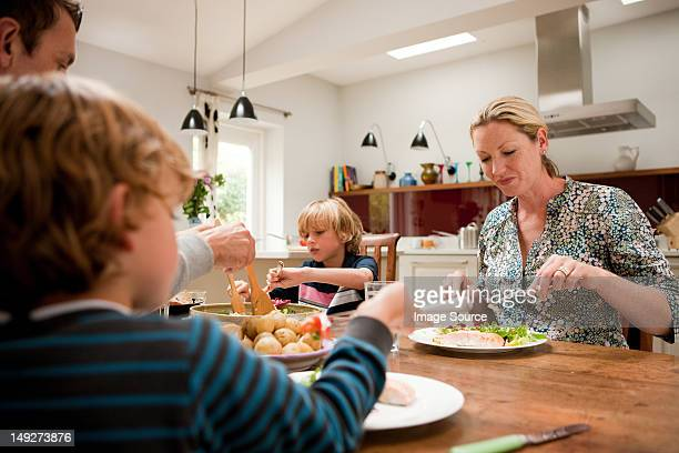Family sitting down and eating a healthy meal together