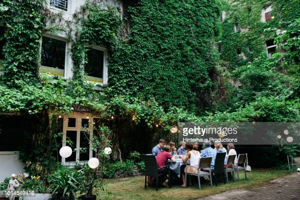 Family Sitting Down For Meal In Courtyard Together