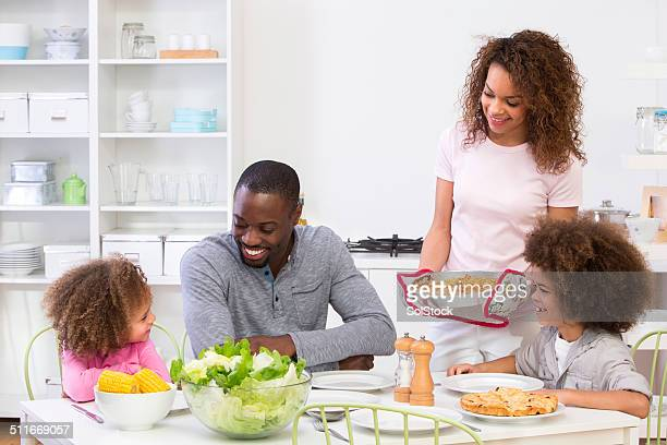 family sitting down to a meal - black family dinner stock photos and pictures