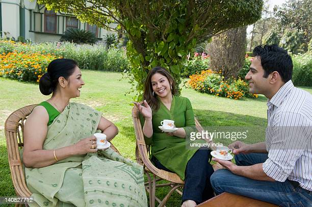 Family sitting in a lawn and drinking tea
