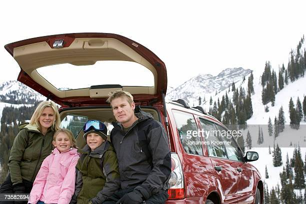 Family sitting in back of parked SUV on ski trip in mountains, smiling, portrait