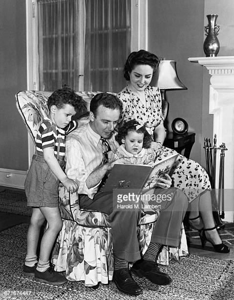 family sitting in chair and reading book - {{ collectponotification.cta }} foto e immagini stock