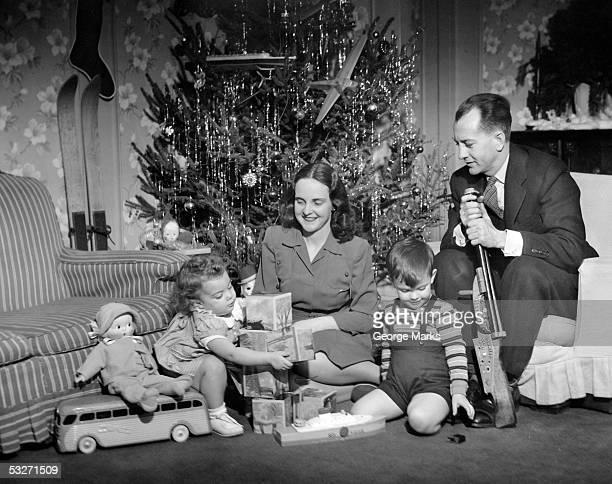 family sitting in front of christmas tree - noel noir et blanc photos et images de collection