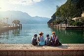Familie sitzen im Hafen von Riva del Garda und genießen die Aussicht auf den Gardasee