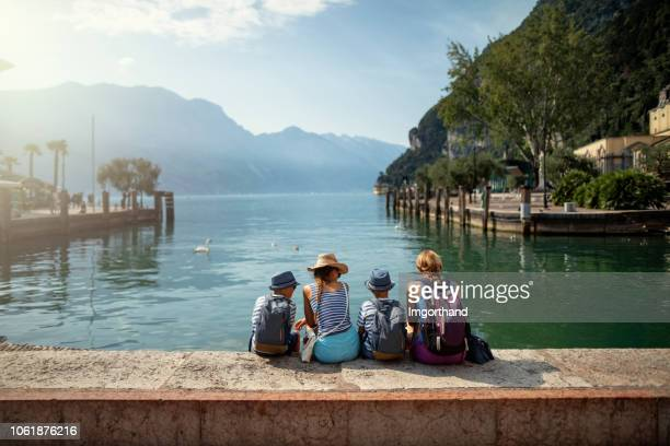 family sitting in harbor of riva del garda and enjoying view of lake garda - férias imagens e fotografias de stock