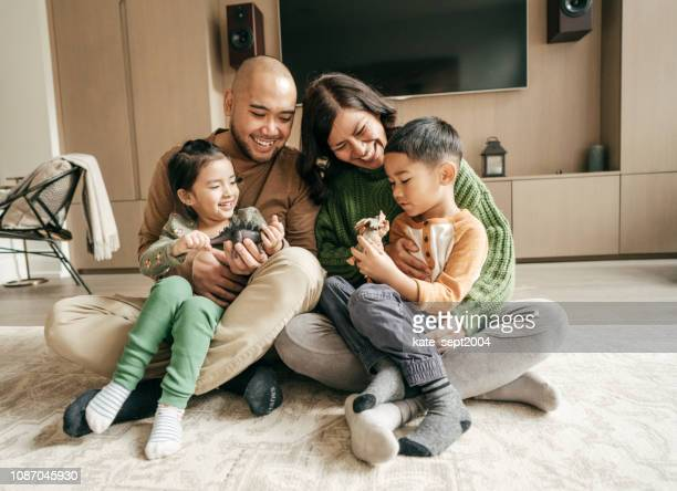 family sitting in the living on the floor - asian and indian ethnicities stock pictures, royalty-free photos & images