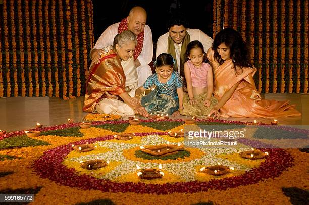 Family sitting near a rangoli