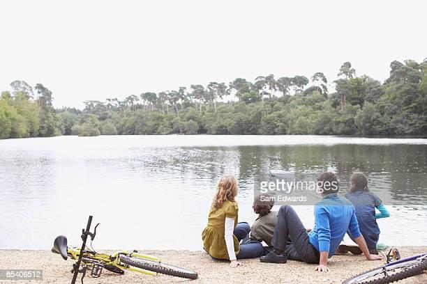 Familie sitzt in der Nähe von See