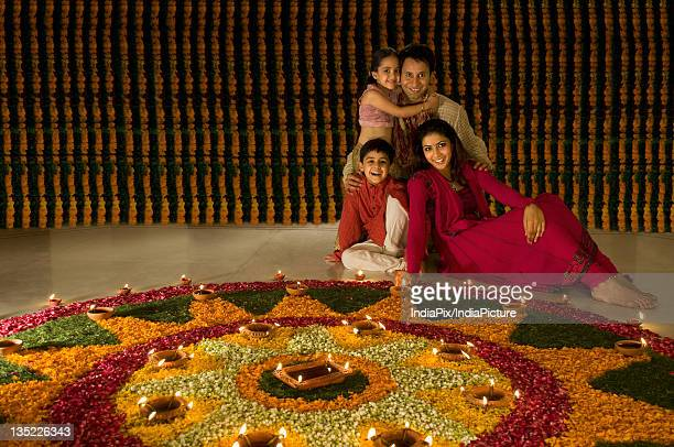Family sitting near rangoli