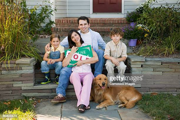 Family sitting next to house with a sold sign