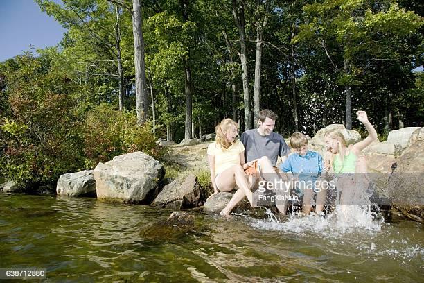 Family sitting next to lake and splashing water