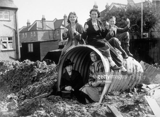 A family sitting on and in their air raid shelter give the thumbs up to a warden who warned them of a delayed action bomb he found in the vicinity of...