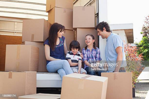 Family sitting on back of moving van