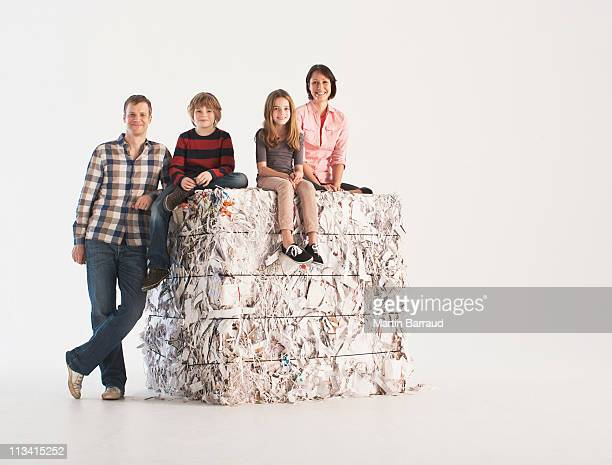 Family sitting on bale of paper, smiling