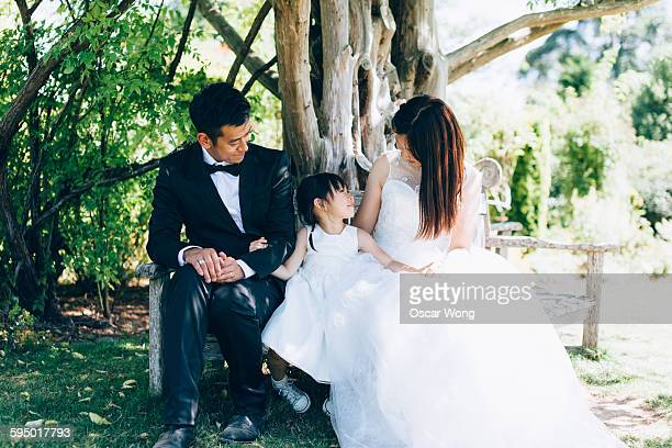 Family sitting on bench in garden