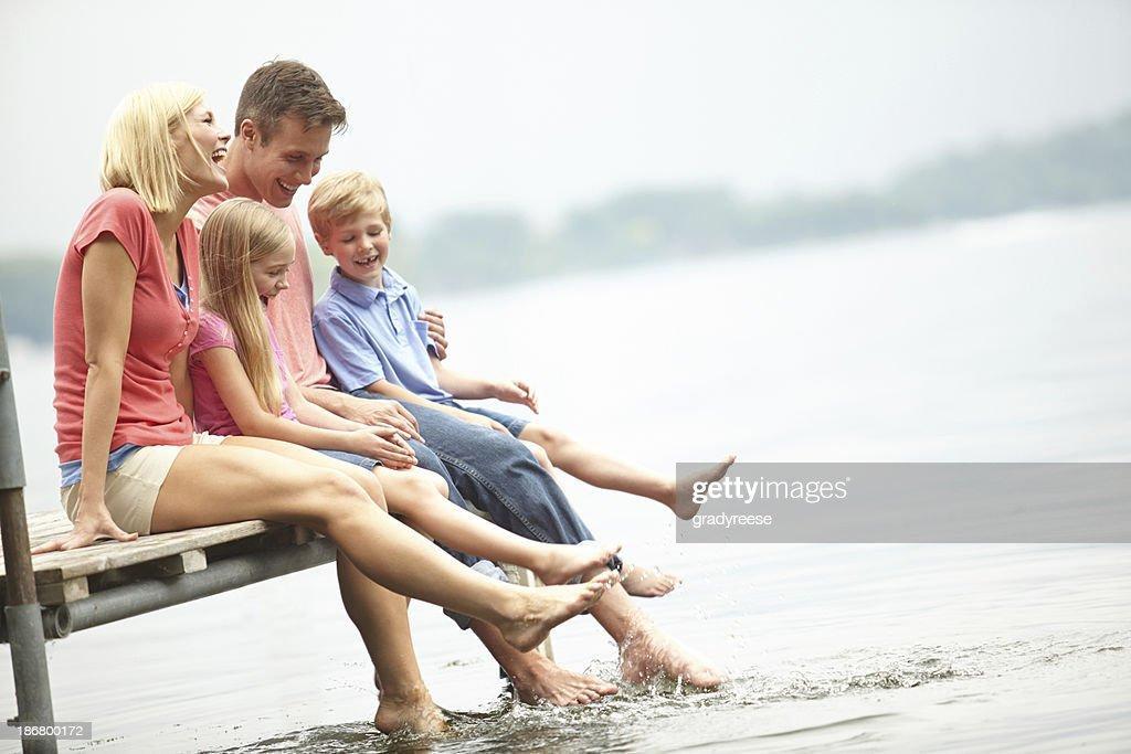 Family sitting on boardwalk at lakeside : Stock Photo