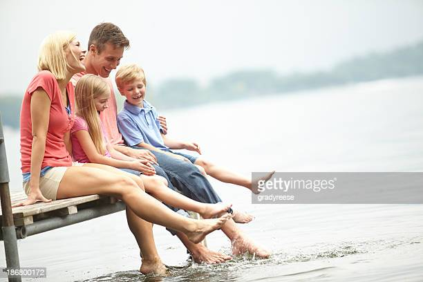 Family sitting on boardwalk at lakeside